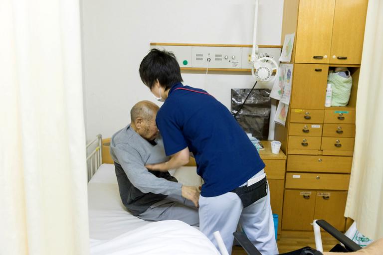 写真:ベッドから体を起こす介助